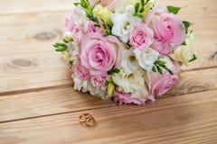 Dwa złocistej obrączki ślubnej i pięknego ślub są na brown drewno stole Zdjęcia Royalty Free