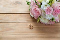 Dwa złocistej obrączki ślubnej i pięknego ślub są na brown drewno stole Obrazy Stock