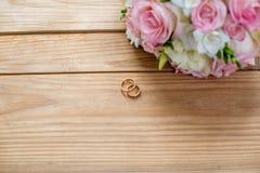 Dwa złocistej obrączki ślubnej i pięknego ślub są na brown drewno stole Zdjęcie Stock