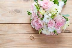 Dwa złocistej obrączki ślubnej i pięknego ślub są na brown drewno stole Fotografia Stock