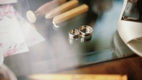 Dwa złocistej obrączki ślubnej kłama na stołu whit dekoracjach błyszczy z światłem zamkniętym w górę makro- Przetaczanie światło  zbiory wideo