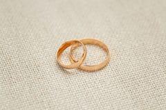 Dwa złotej obrączki ślubnej na beżowym tle, zamykają up Obrazy Royalty Free