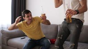 Dwa z podnieceniem dorosłego przyjaciela pije piwo i ogląda mecz futbolowego salowego na telewizorze z interesem Wstają od kanapy zbiory wideo