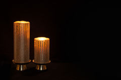 Dwa zaświecającej świeczki przeciw ciemnemu beackground obrazy stock