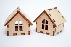 Dwa zabawki drewniany dom na białym tle, jeden mieści wyjawiony z ukosa pojęcie sprzedaż domy zdjęcia royalty free