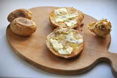 Dwa Zaokrąglali plasterki chleb z masłem, dwa piec grulami i suchą biel różą na Drewnianym Chopboard, fotografia stock