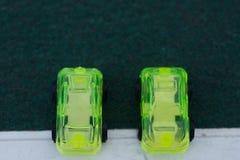 Dwa zielonego plastikowego samochodu na zaczyna linii symbolizuje środowiskowego afekt automobilowy przemysł fotografia stock
