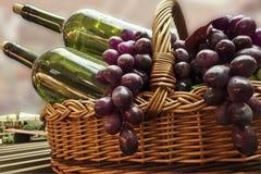 Dwa zielonej butelki wino w koszu z winogronami Fotografia Royalty Free