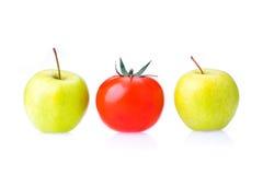 Dwa zielonych Apple i czerwonych jeden pomidoru Fotografia Stock