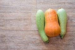 Dwa zucchini i jeden bania na drewnianym tekstury tle skład zdjęcia stock