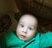 Dwaas gezicht van kleine baby met blauwe ogen stock foto