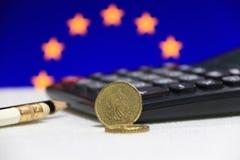 Dwadzieścia Francja euro cent na awersie na białej podłoga z czarnym kalkulatorem ołówkiem i, Europejska Zrzeszeniowa flaga obraz stock