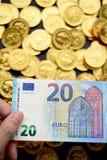 Dwadzieścia euro na ręce i złocistych monetach Zdjęcie Royalty Free