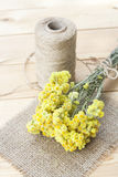 Dwarf everlast flowers bouquet, napkin and twine bobbin on light wooden table Royalty Free Stock Photography