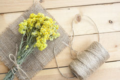 Dwarf everlast flowers bouquet, napkin and twine bobbin on light wooden table Stock Images