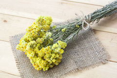 Dwarf everlast flowers bouquet, napkin and twine bobbin on light wooden table Stock Photography