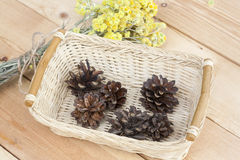 Dwarf everlast flowers bouquet and pine cones in a wicker basket on light wooden table Royalty Free Stock Photography