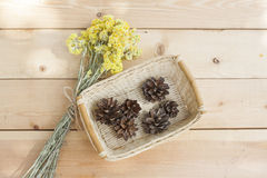 Dwarf everlast flowers bouquet and pine cones in a wicker basket on light wooden table Royalty Free Stock Photos