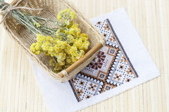 Dwarf everlast flowers bouquet in a wicker basket and napkin with embroidery on light wooden table Royalty Free Stock Photo