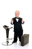 Dwarf, little businessman. Little businessman, dwarf in a formal suit with bow tie next to bar stool and suitcase, studio shot, white background Stock Photos