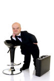 Dwarf, little businessman. Little businessman, dwarf in a formal suit with bow tie next to bar stool and suitcase, studio shot, white background Royalty Free Stock Photos