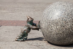 Dwarf pushing a granite ball in Wroclaw Royalty Free Stock Photo