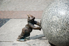 Dwarf pushing stone ball Wroclaw Poland. Dwarf pushing big and heavy sphere Royalty Free Stock Image