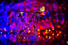 A dwarf or Santa Claus climbed onto a crystal ice bucket against Stock Photo