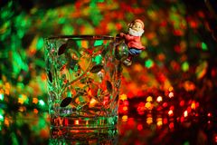 A dwarf or Santa Claus climbed onto a crystal ice bucket against Royalty Free Stock Images