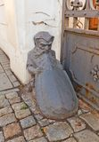 Dwarf shape old wheel guard (bollard) in Lodz, Poland. Old wheel guard (bollard) in the shape of dwarf with a shield near historic house (XIX c.) in Lodz, Poland Stock Images