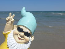 Funny garden gnome with sunglasses seaside makes peace sign. Dwarf with blue hat and  sunglasses seaside Royalty Free Stock Photos