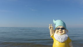 Funny garden gnome with sunglasses seaside makes peace sign. Dwarf with blue hat and  sunglasses seaside Stock Photos