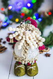 Dwarf, a toy on a white wooden table on green background Christmas and New Year`s garland of colored lights Royalty Free Stock Images