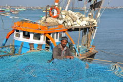 DWARKA, GUJARAT, INDIEN - 26. DEZEMBER 2013: Fischer, der an seinem Fischernetz in Bet Dwarka Island nahe Dwarka arbeitet Stockbild