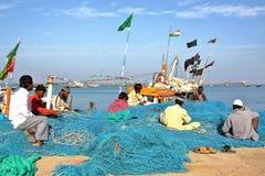 DWARKA, GUJARAT, INDIEN - 26. DEZEMBER 2013: Fischer, die an ihrem Fischernetz in Bet Dwarka Island nahe Dwarka arbeiten Stockbild