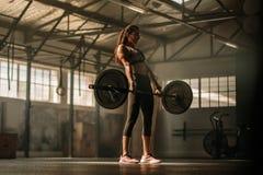 Dwars geschikte vrouw die zware gewichten in gymnastiek opheffen royalty-vrije stock fotografie