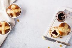 Dwarsdiebroodjes met rozijnen, met boter en jam voor Pasen worden gediend stock foto
