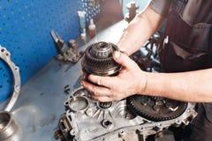 Dwarsdoorsnede van een autoversnellingsbak het werktuigkundigenwerk in de garage handwerktuigkundige in werkkledij Stock Foto's