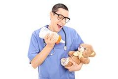 Dwaze mannelijke arts het voeden melk aan een teddybeer Royalty-vrije Stock Foto's