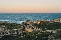 Dwejra Bay at sunrise, Gozo, Malta. Island of Gozo, Malta. Dwejra Bay at sunrise with ancient stone bridge which leads the road to Azure Window Stock Photography
