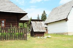 Dwell in open-air museum. Wooden dwell with winch among old white village houses with shingles roofs in open-air museum Liptov Village Museum Pribylina in Stock Images