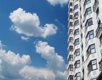 Dwelling, apartment house. Modern apartment house against the sky with clouds in a city Stock Image