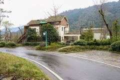Dwelling building by mountainside road after rain Royalty Free Stock Photos