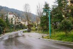 Dwelling buildings along curving asphalt mountain road after rai Stock Photo
