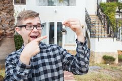 Dwelling, buying home, real estate and ownership concept - handsome man showing his key to new home stock photography