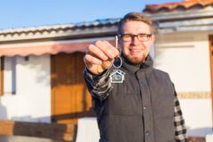 Dwelling, buying home, real estate and ownership concept - handsome man showing his key to new home stock image