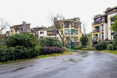 Dwelling houses along curving tarred road after rain. Dwelling buildings along curving asphalt road after the rain Stock Image