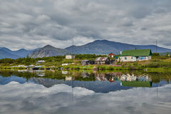 Dwelling of meteorologists on island. Reflexion in water. Jack London's lake. Kolyma Stock Photo