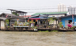 Dwellings of poor people on the embankment to Bangkok Stock Photo