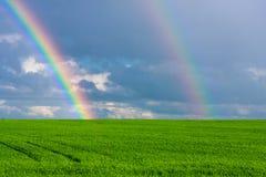 Dwoista tęcza w błękitnym chmurnym dramatycznym niebie nad zielonym polem iluminującym słońcem w kraj stronie banatka Zdjęcie Royalty Free